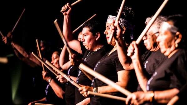 Taste of Taiko, a group of black and brown skin adults drumming on stage